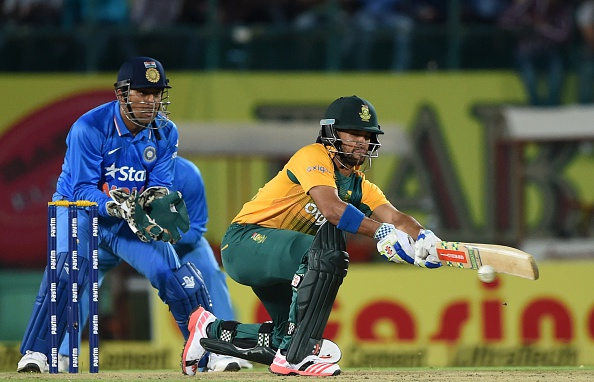 South Africa's JP Duminy (R) plays a shot as India's captain Mahendra Singh Dhoni looks on during the first T20 cricket match between India and South Africa (Photo credit should read PRAKASH SINGH/AFP/Getty Images)
