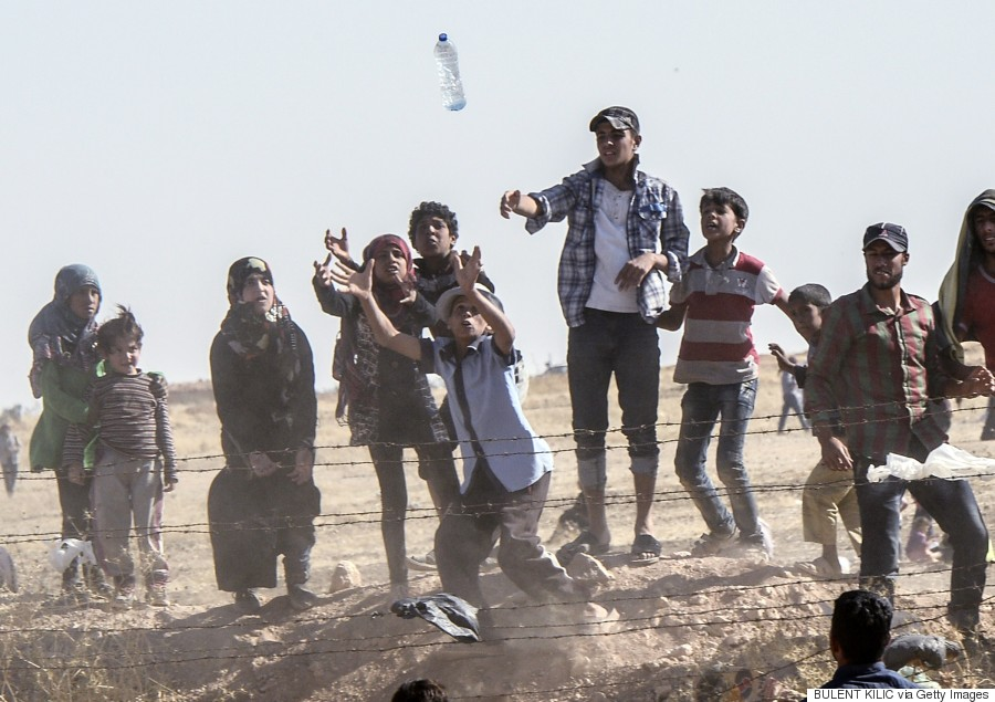 "Syrian refugees try to grab bottles of water thrown from Turkish side near the Syrian town of Tal Abyad, at Akcakale in Sanliurfa province, on June 12, 2015. Turkey said it was taking measures to limit the flow of Syrian refugees onto its territory after an influx of thousands more over the last days due to fighting between Kurds and jihadists. Under an ""open-door"" policy, Turkey has taken in 1.8 million Syrian refugees since the conflict in Syria erupted in 2011. AFP PHOTO / BULENT KILIC        (Photo credit should read BULENT KILIC/AFP/Getty Images)"